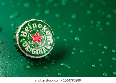 New York, UNITED STATES OF AMERICA - February 20, 2020: classic cap close-up of Heineken on a green background with drops of water.