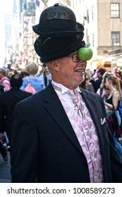 "New York, New York / United States - April 16, 2017: Man wearing black hats and a green apple in an homage to the René Magritte painting ""The Son of Man"" at the Fifth Avenue Easter Parade."