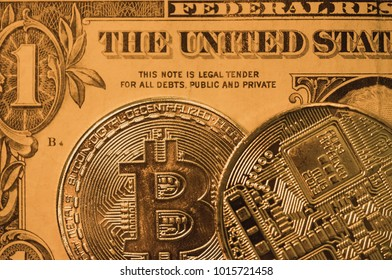 New York, United States - Circa January 2018: Macro view of a pair of Bitcoin coins showing the surface detail of the coinage, with a golden light in the subject. The coins are seen on a Dollar bill.