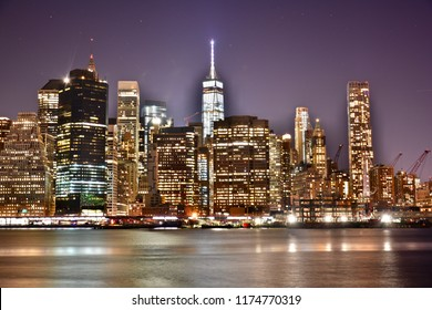 New York, United States - December 30, 2016:  New York City Manhattan downtown skyline with skyscraper and water reflection over East River at night