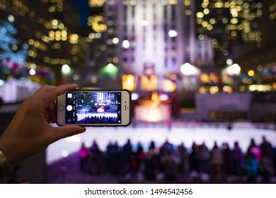 New York, United States, December 23 2018. A tourist is taking pictures with his phone at the Rockefeller tower in New York, USA. Rockefeller Plaza is an American Art Deco skyscraper.