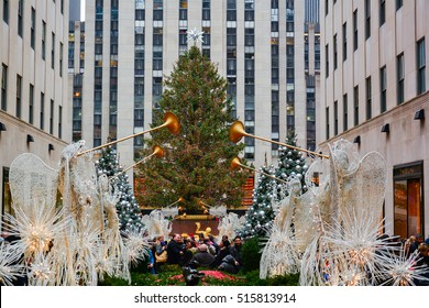 NEW YORK, UNITED STATES - DECEMBER 29, 2015 - The Rockefeller Center Christmas Tree shines brightly as people ice skate below on the famous Rockefeller Center rink in the evening.