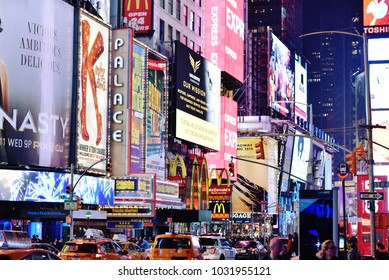 NEW YORK, UNITED STATES - FEB 20: Advertisements cover buildings in Time Square during night, with lights illuminating street, February 20th, 2018.