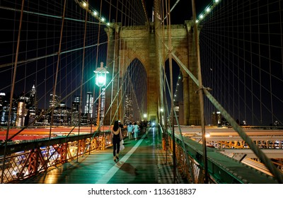 NEW YORK, UNITED STATES, JUNE 18, 2018: people walking on Brooklyn bridge footpath, while traffic cars goes under,  with Manhattan skyline illuminated at night, in New York.