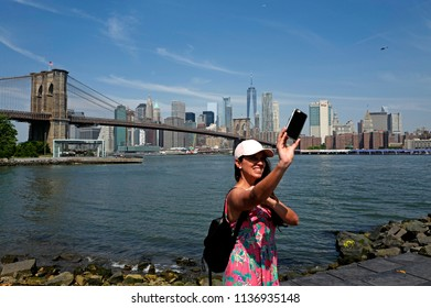 NEW YORK, UNITED STATES, JUNE 18, 2018: selfie girl with Brooklyn bridge and Manhattan skyline in the background, in New York.