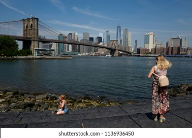 NEW YORK, UNITED STATES, JUNE 18, 2018: blonde girl back with Brooklyn bridge and Manhattan skyline seen from the Brooklyn park, in New York.