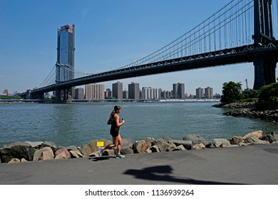 NEW YORK, UNITED STATES, JUNE 18, 2018: girl jogging under the Manhattan bridge on the Brooklyn park, in New York.