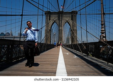 NEW YORK, UNITED STATES, JUNE 18, 2018: businessman crossing the Brooklyn bridge on the walk path, in New York.