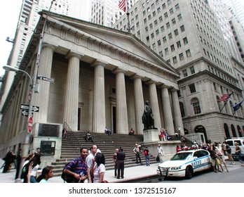 New York, New York / United States - June 10 2006:  The Federal Hall museum on Wall Street in Manhattan New York City with people walking by and an NYPD police car parked in front.