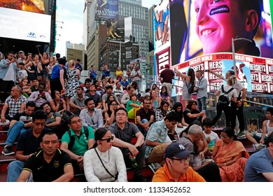 NEW YORK, UNITED STATES, JUNE-17, 2018: tourists gathering at Times Square when the lights are turned on, sunset in Manhattan, in New York.
