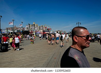 NEW YORK, UNITED STATES-JUNE 18, 2018: people on Coney Island boardwalk, during an hot summer's sunday afternoon, in New York.