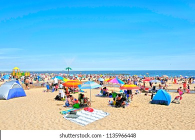 NEW YORK, UNITED STATES-JUNE 18, 2018: sun umbrellas at Coney Island beach, during an hot summer's sunday afternoon, in New York.