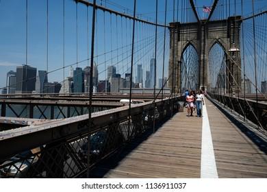 NEW YORK, UNITED STATES-JUNE 18, 2018: Brooklyn bridge walk path and bike lane, with summer blu sky over Manhattan skyline, in New York.