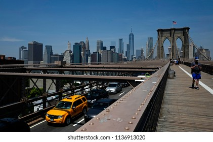 NEW YORK, UNITED STATES-JUNE 18, 2018: nyc yellow cab crossing the Brooklyn bridge, with summer blu sky over Manhattan skyline, in New York.