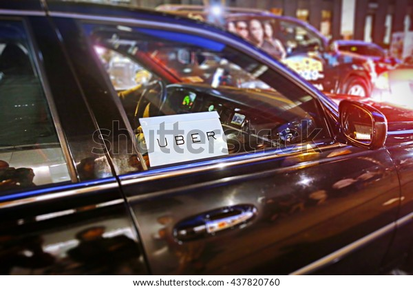 New York, US - August 23, 2015.  Uber car service on the streets of New York at Night. With selective focus on Uber logo.