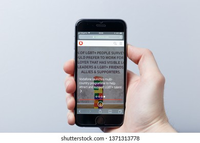 New York / USA - 04.14.2019: A hand holding a smartphone which displays Vodafone Group logo on the official website homepage. Vodafone logo visible on smartphone screen. Illustrative editorial