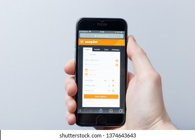 New York / USA - 04.14.2019: A hand holding a smartphone which displays EasyJet logo on the official website homepage. EasyJet logo visible on smartphone screen. Illustrative editorial