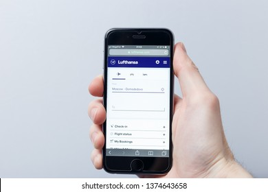 New York / USA - 04.14.2019: A hand holding a smartphone which displays Lufthansa logo on the official website homepage. Lufthansa logo visible on smartphone screen. Illustrative editorial