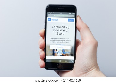 New York / USA - 04.14.2019: A hand holding a smartphone which displays American Express logo on the official website homepage. Logo visible on smartphone screen. Illustrative editorial