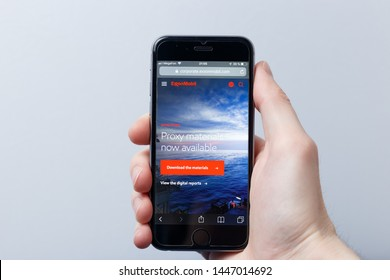 New York / USA - 04.14.2019: A hand holding a smartphone which displays Exxon Mobil logo on the official website homepage. Exxon Mobil logo visible on smartphone screen. Illustrative editorial
