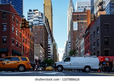 New York, New York / USA - 06 06 2018: Manhattan streets, buildings, skyscrapers, traffic and pedestrians.