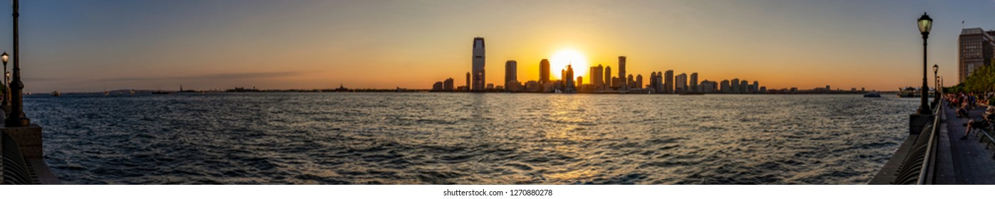 New York / USA - 06-01-2016; A panorama photo during sunset looking from Hudson River Greenway on the Hudson River and the sun setting between the sky-line of Jersey City, New York, USA