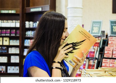 New york, new york, USA 08 03 2016: Beautiful latin teenager smiling and  smelling a new book  for World book day at a bookstore