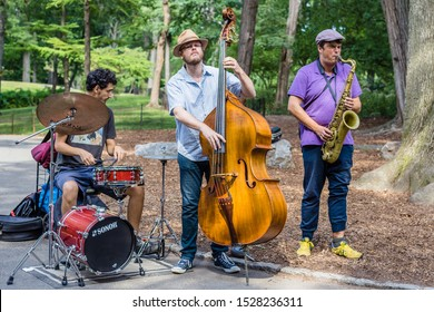 New York, USA - 10 September 2014:  Colour image of a jazz band trio playing music in Central Park, mid-town Manahattan, NYC.