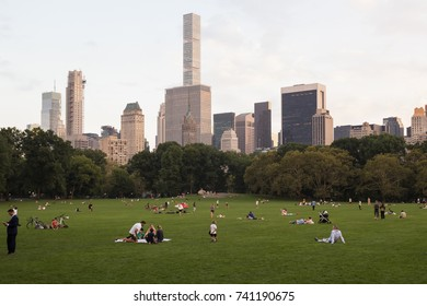 NEW YORK, USA - 14 of October 2017: Many people rest on the grass lawn of Central park, skyscrapers peeks out of the trees on background