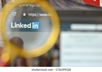 New York, USA, 2020. Linkedin website signup page through a magnifying lens. Out of focus laptop screen is in the background. Concept social network