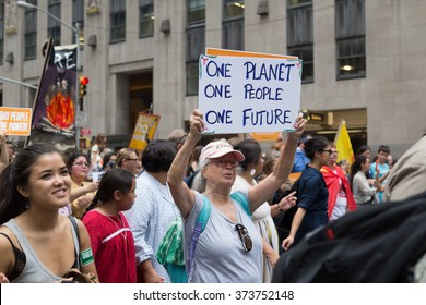 New York, USA - 21 September 2014.  Woman carries a placard and demonstrates for environmental awareness during the 2014 People's Climate March through Manhattan, New York, USA.