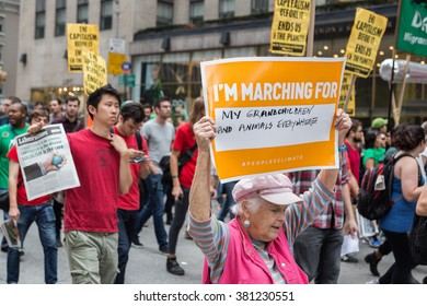 New York, USA - 21 September 2014:  Grandmother carries a banner whilst marching and campaigning for greater environmental awareness during the Peoples Climate March through New York City