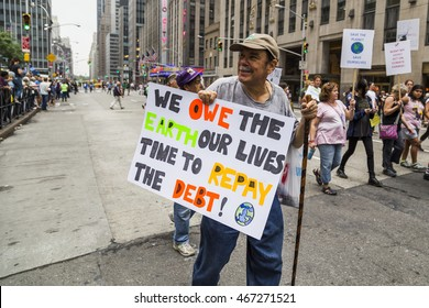 New York, USA - 21 September 2014.  Man carries a placard stating 'We owe the Earth our lives, time to repay the debt' during the 2014 People's Climate March, New York, USA.