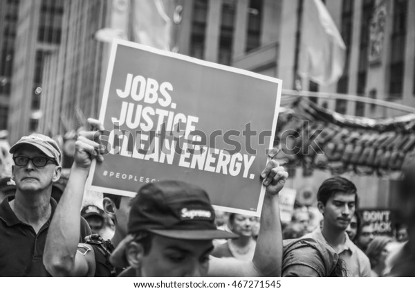 New York, USA - 21 September 2014.  Black and white image of a person carrying a placard supporting 'Jobs, Justice, Clean Energy' during the 2014 People's Climate March, New York, USA.