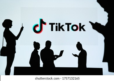 NEW YORK, USA, 25. MAY 2020: TikTok, Chinese video-sharing social networking service Group of business people chat on mobile phone and laptop. Company logo on screen in background