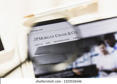 New York, USA - 27 February 2019: JPMorgan Chase Co. official website homepage under magnifying glass. Concept JPMorgan Chase Co. logo visible on smartphone, tablet screen