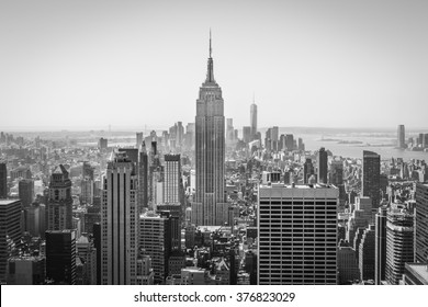 New York, USA -  4 September 2014:  Monochrome image of the Empire State Building and Lower Manhattan during a clear day in summer with the One World Trade Center and Liberty Island in the distance.
