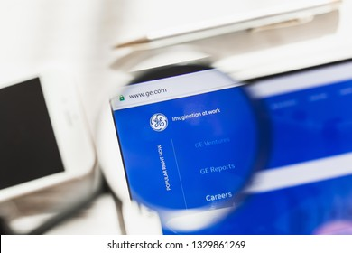 New York, USA - 6 March 2019: General Electric, GE official website homepage under magnifying glass. Concept General Electric, GE logo visible on smartphone, tablet screen,