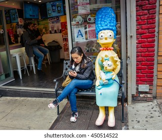 NEW YORK, USA - Apr 28, 2016: Girl with a mobile phone near a cafe in Chinatown. The Americans on the streets of Manhattan in NYC