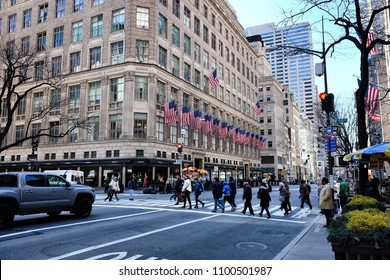 New York, USA, April 08, 2018: Saks Fifth Avenue, American  department store decorated with USA flags in Midtown Manhattan. People on a crosswalk crossing the road
