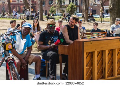 NEW YORK, USA - APRIL 14, 2018: Men singing and playing the piano in the park near with West Village, New York City, USA
