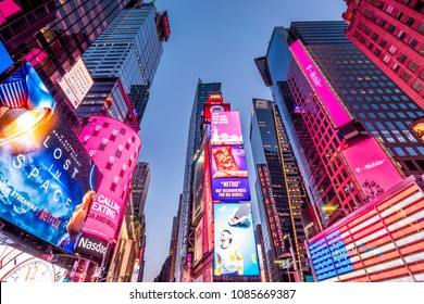 NEW YORK, USA - APRIL 20, 2018: The architecture of New York city in the USA at Times Square with its neon signs, stores, chaotic traffic, and tons of tourists and locals passing by.