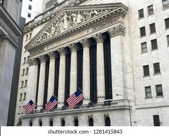 New York, USA - april 21, 2018. Facade of the New York Stock Exchange on the Wall Street, patriotic us flags. Architecture building of the Wall Street, sightseeing.