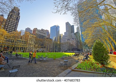 NEW YORK, USA - APRIL 24, 2015: Tourists relaxing in Bryant Park in Midtown Manhattan, New York, USA. Skyscrapers on the background