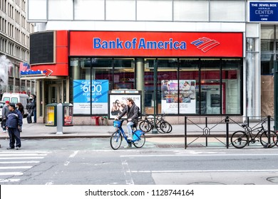 New York, USA - April 7, 2018: Street view on Bank of America branch in NYC with people waiting, pedestrians crossing, crosswalk, bike, road in Manhattan