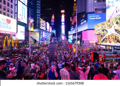 New York, USA - Aug 10, 2018: Many people at Time Square with colorful light in the night, view from George M Cohan monument.