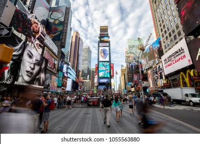 New York, USA - Aug 17, 2016: Times Square in daytime with One Times Square (Times Tower) in the middle surrounded with buildings and billboards and people walking on the street
