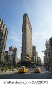 NEW YORK, USA - AUGUST 06, 2014: Yellow taxis head downtown on Broadway past the Flatiron Building, one of the city's first and most iconic skyscrapers.