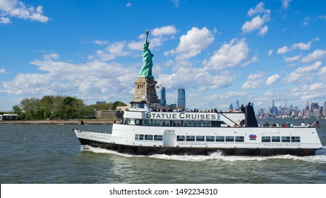 New York, USA. August 1, 2019. White cruiser boat in front of the Statue of Liberty. Summer time. Tourist attraction. Boat heads to the pier of the Liberty Island
