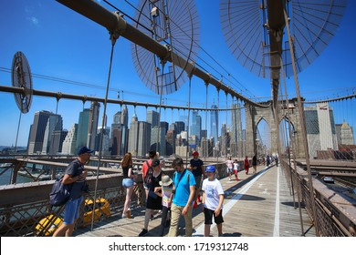 New York, USA – August 23, 2018: People on pedestrian walkway on the Brooklyn Bridge, this bridge connects Manhattan and Brooklyn and is one of the biggest suspension bridge in the world.